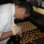 Piping the butter cream on bottom of macarons